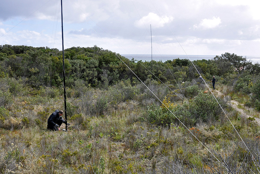 Chris G3SVL at the base of the 160m antenna at ZL7G with a receive antenna in the back-ground.